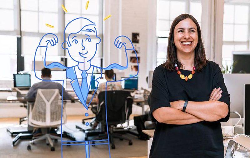 insuffler de la motivation : femme souriante sur son lieu de travail en position debout les bras croisés