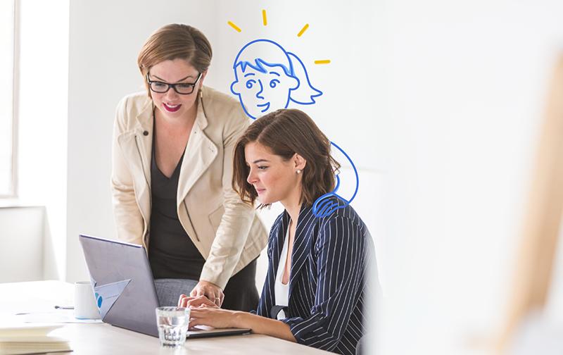 Bienveillance, deux femmes souriantes discutant autour d'un écran d'ordinateur