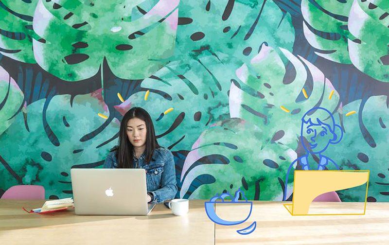 la qualité de vie au travail : femme travaillant sur un ordinateur, avec un tasse à café, devant un mur coloré