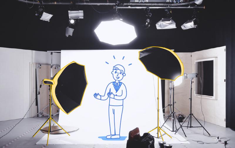 vaincre le burnout : un studio de photographie avec un bonhomme souriant dessiné sous les projecteurs