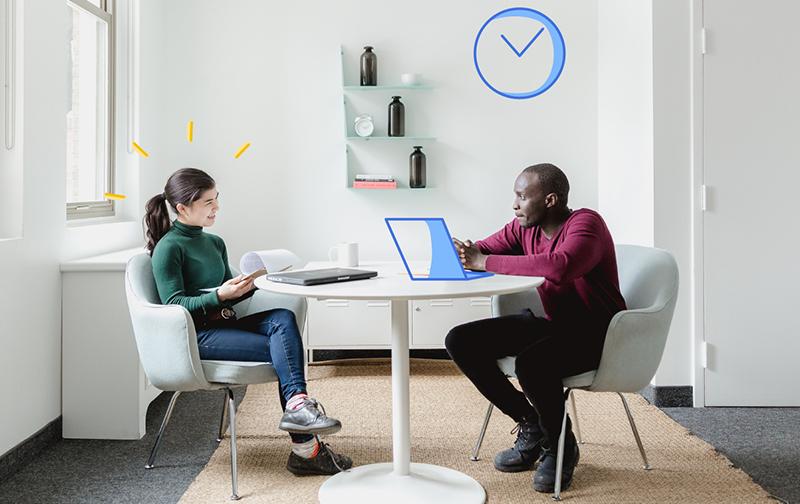le bien-être au travail un homme et une femme assis à un table avec des ordinateurs et discutant