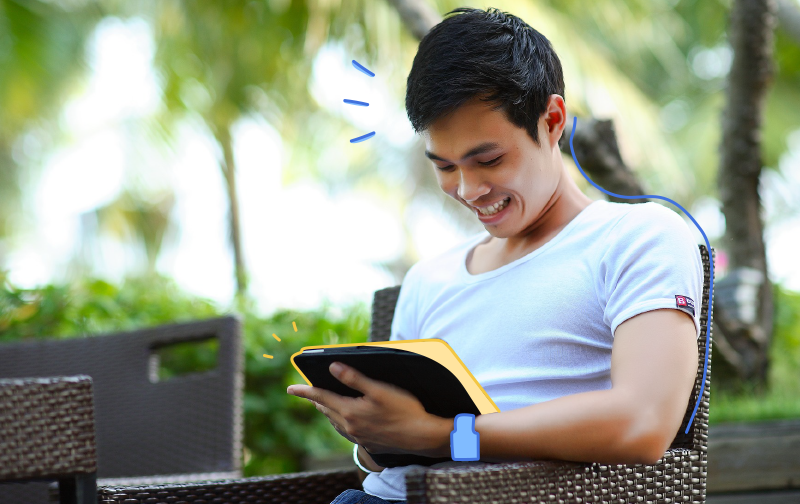 améliorer la qualité de vie au travail : homme assis dehors sur un chaise souriant avec une tablette à la main