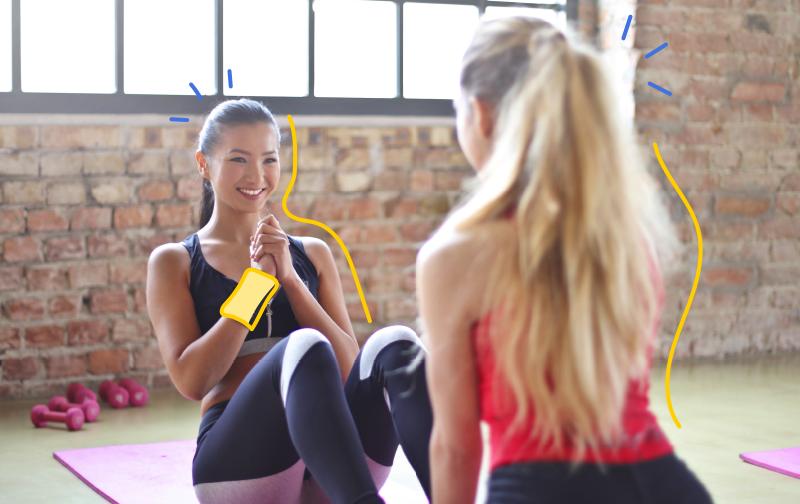 sport au bureau, une fille sur un tpais de yoga qui fait des pompes pendant qu'une autre fille la tiens par les pieds.