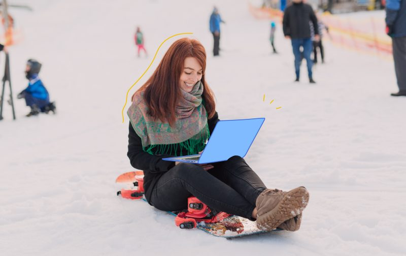 addiction au travail, une femme assise sur une luge sur la neige avec un ordinateur portable sur les genoux