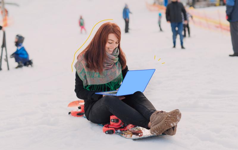 l'addiction au travail, une femme assise sur une luge sur la neige avec un ordinateur portable sur les genoux