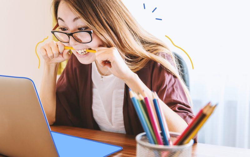 soft skills, une femme assise à son bureau devant son ordinateur mordant un stylo
