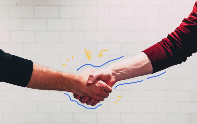 conflit au travail, zoom sur les avants bras de deux hommes se serrant la main