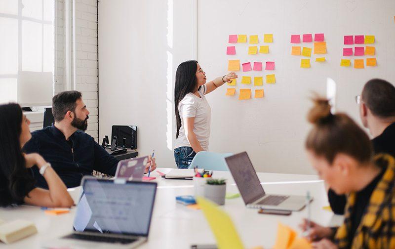 attentes des collaborateurs, salle de réunion avec fille qui pointe sur un mur rempli de post-it de plusieurs couleurs