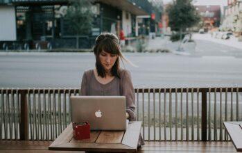 bore-out, une femme à une terrasse de café travaillant sur son ordinateur
