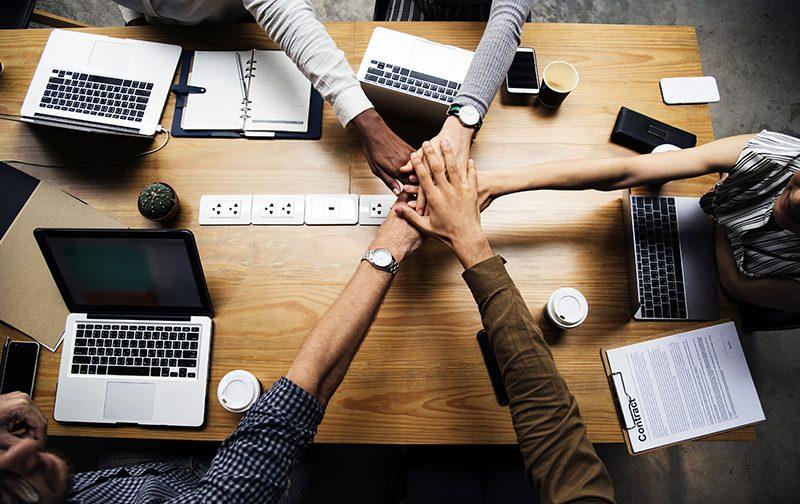 manque d'équité, 5 personnes tendent leurs bras en avant pour symboliser l'esprit d'équipe