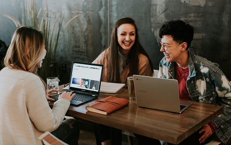 développement personnel, trois jeunes adultes autour d'une table entrain de rire