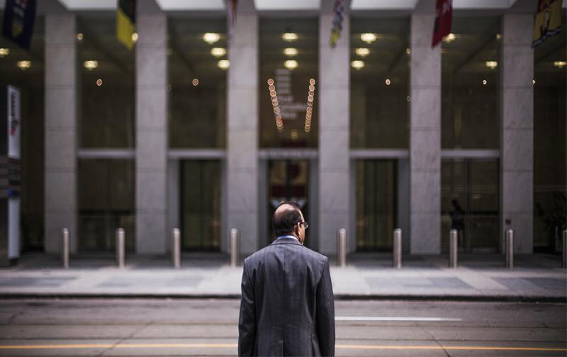 justice organisationnelle, cinquantenaire en costume de dos devant un immeuble de bureaux