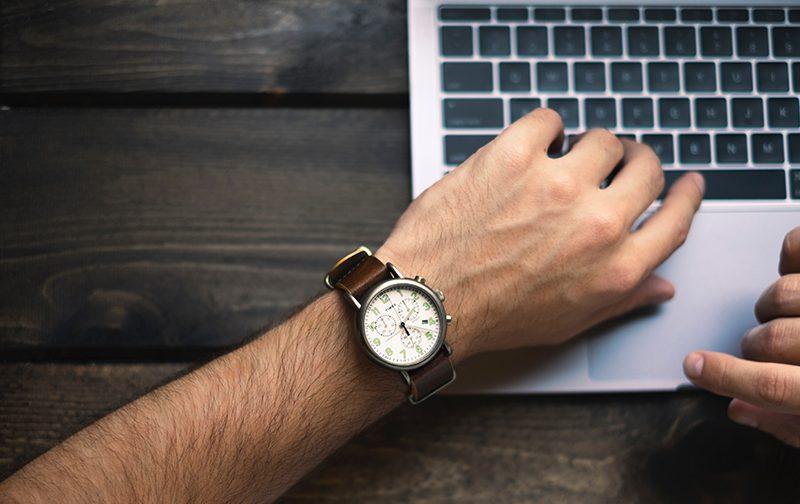 manque de temps, poignet d'homme avec une montre en cuir marron