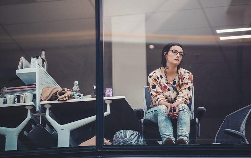 Femme pensive et inquiète d'un changement en entreprise, regardant à travers la fenêtre de son bureau
