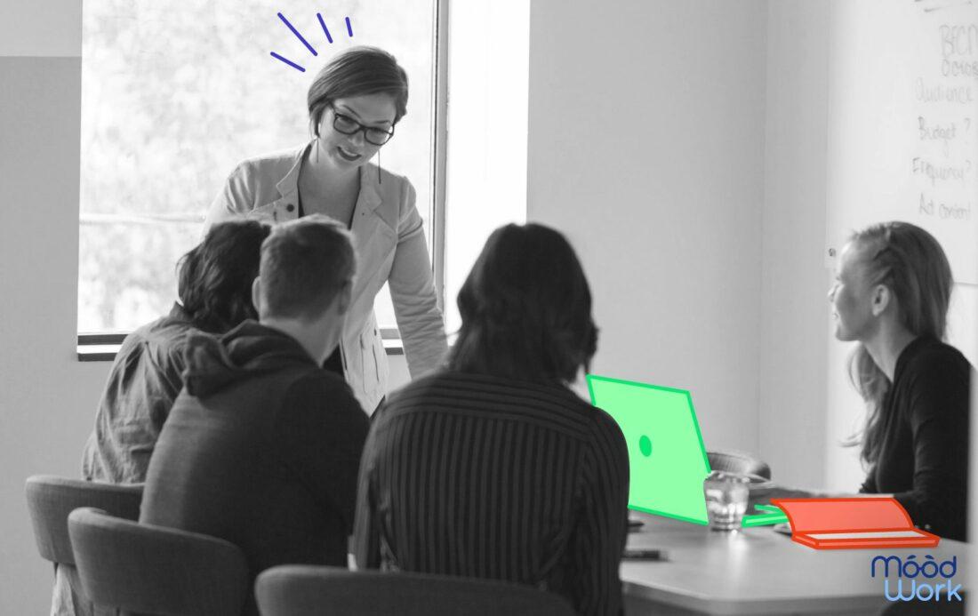 codir autour d'une table en reunion, femme debout souriante
