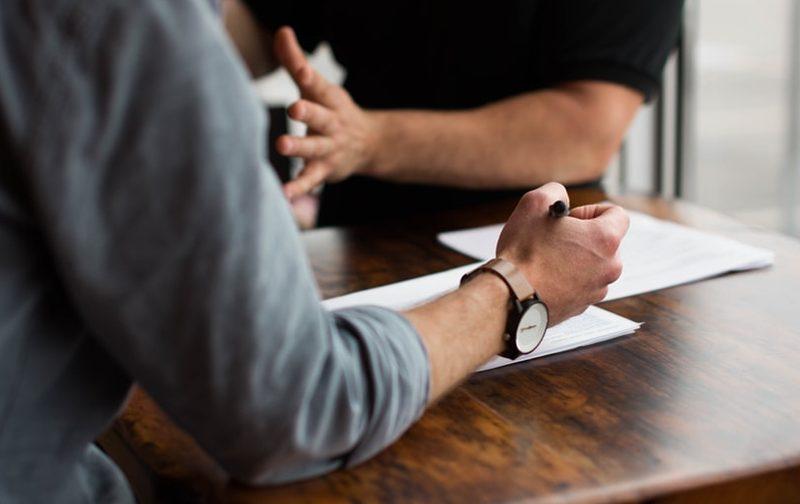 la QVT dans le monde du conseil, deux hommes discutant autour d'une table en bois avec des bloc-notes