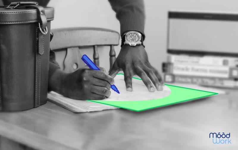 DUERP main d'homme écrivant sur un carnet avec une montre
