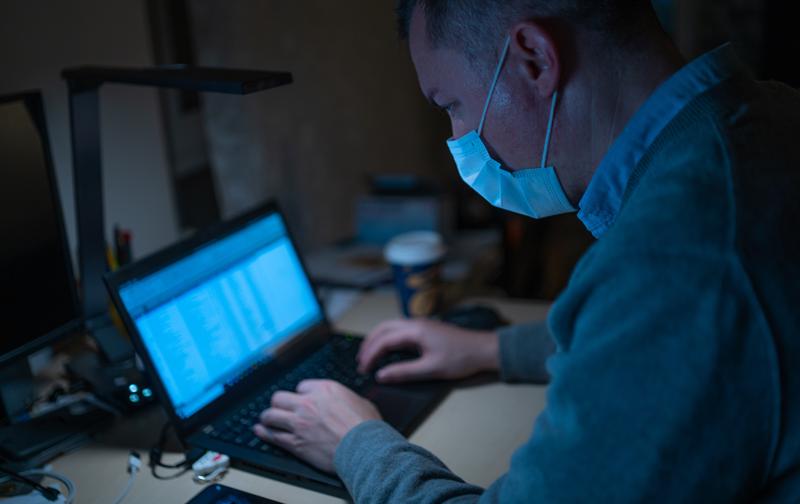 coronavirus en entreprise, homme tapant sur son ordinateur avec un masque, crédit photo : dimitri karastelev