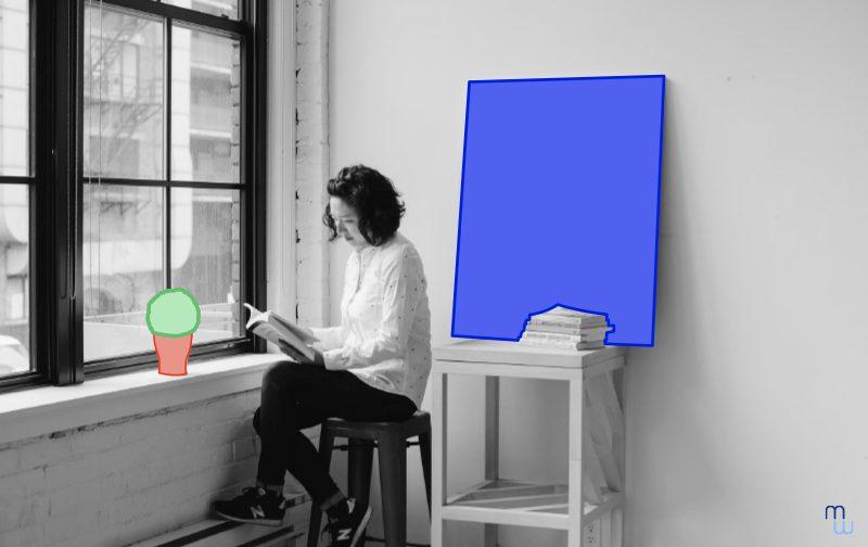 la marque employeur : une femme qui lit un livre assise sur un tabouret devant une fenêtre